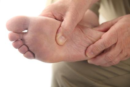 Massage Therapy Kelowna - a man checks his aching foot